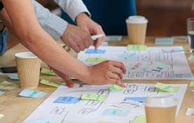 team collaboration. Close up of hands moving post it notes around a written diagram on a table