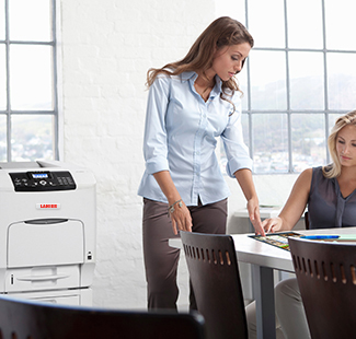 Woman standing at desk with Lanier printer in background