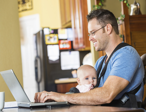 Father with baby working on a laptop at home.