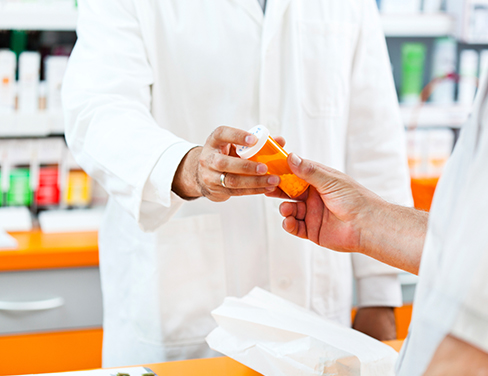 Pharmacist giving medication to customer.