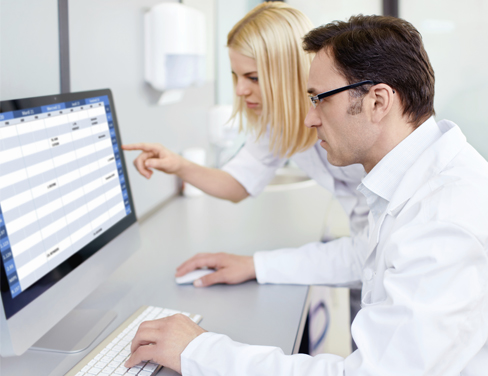 Two doctors reviewing information on a computer.