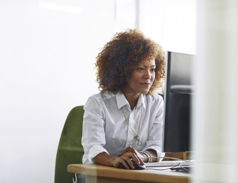 African american female office clerk using desktop computer.