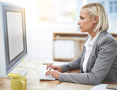 Ricoh - professional woman at her desk reviewing documents on her large monitor