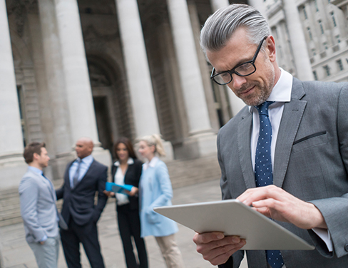 Ricoh - Male lawyer at the front of a courthouse on his tablet