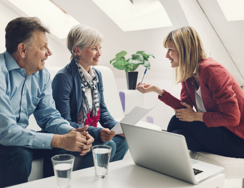 Ricoh professional providing advice to older couple with laptop in front