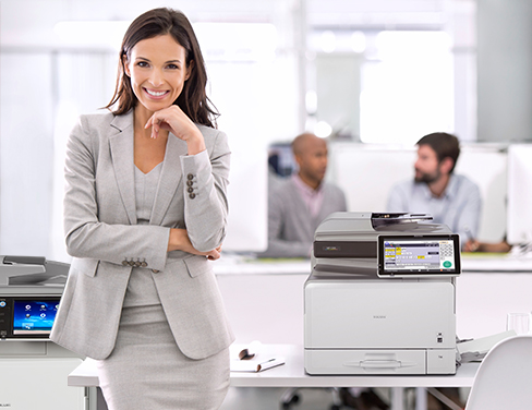 Woman in office and grey suit with multiple RICOH printers