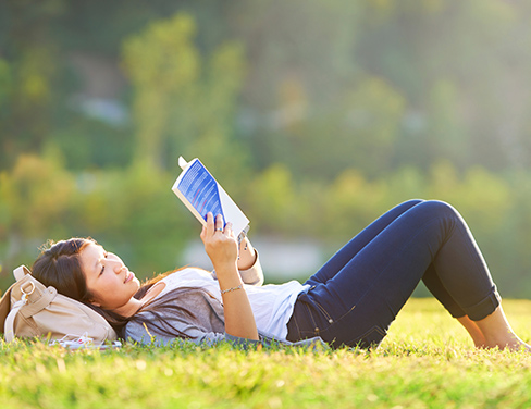 Student laying on her back in the grass reading