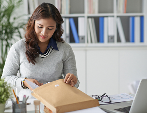 Ricoh - Lady in grey sweater preparing a package at her desk