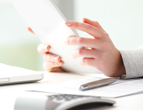 Ricoh - close-up of woman holding her tablet with calculator and pen at desk