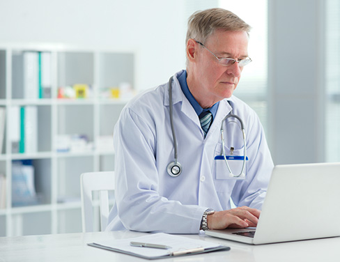 Photo of a doctor in his office on a laptop