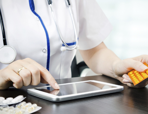 Close up of doctor using a tablet