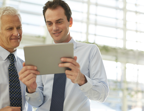 Two businessmen looking at a tablet device.