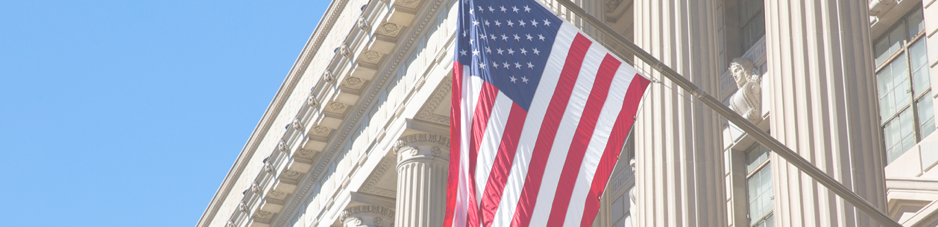 Close up of USA flag with courthouse columns in background and blue sky